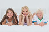 Siblings and mother lying on bed
