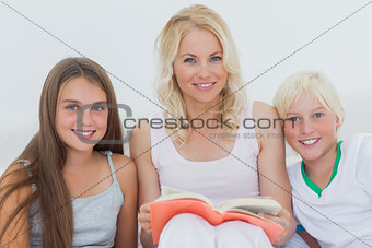 Portrait of mother holding a storybook to her children