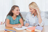 Cheerful mother and daughter writing together