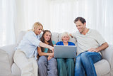 Family sitting on a couch while using a laptop