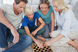 Portrait of a cute family playing chess