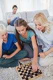 Siblings and mother playing chess sitting on a carpet