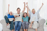 Family watching television and raising arms
