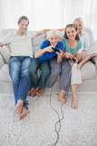 Children playing video games together sitting on the couch