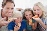 Smiling family eating pizza