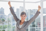 Excited businesswoman cheering and smiling