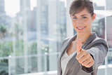 Smiling businesswoman giving thumb up at camera