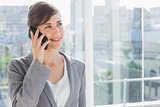Businesswoman smiling and calling on phone