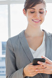 Businesswoman texting and smiling