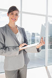 Businesswoman holding laptop and smiling