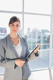 Businesswoman holding clipboard and smiling at camera