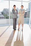 Confident businesswomen standing in bright office