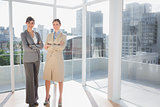 Smiling businesswomen standing in bright office