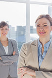 Happy businesswomen with arms crossed smiling at camera