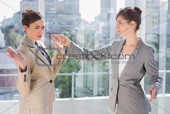 Annoyed businesswoman pointing at her rival