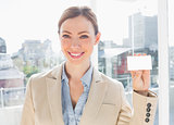 Smiling businesswoman showing blank business card