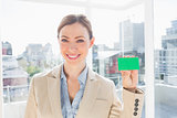 Smiling businesswoman showing green business card