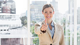 Smiling businesswoman giving thumb up to camera