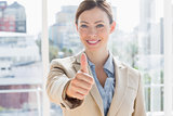 Happy businesswoman giving thumb up to camera