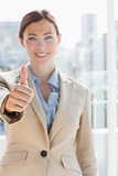 Pretty businesswoman giving thumb up to camera