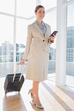 Businesswoman walking with suitcase and checking her phone