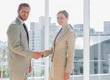 Business people shaking hands and smiling at camera