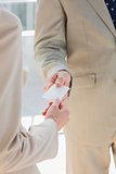 Businessman handing card to businesswoman