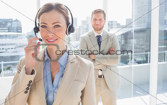 Call centre worker standing with colleague behind her