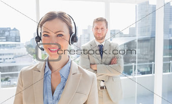 Call centre agent standing with colleague behind her