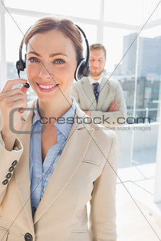 Call centre agent smiling with colleague behind her