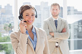 Happy call centre agent with colleague behind her