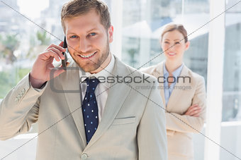Smiling businessman on the phone looking at the camera