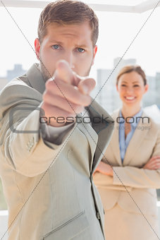 Annoyed businessman pointing at camera