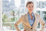 Pretty businesswoman smiling at camera with hands on hips