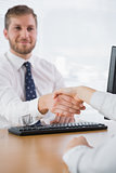 Smiling businessman shaking hands with a co worker