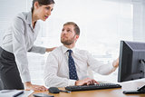 Businessman showing his co worker something on computer