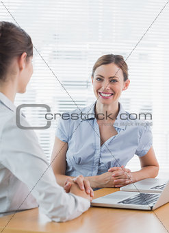 Attractive businesswoman smiling at camera with her colleague