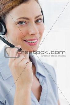 Call centre agent wearing headset smiling at camera