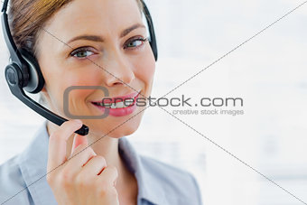 Call centre operator wearing headset smiling at camera
