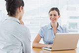 Businesswoman smiling at interview candidate