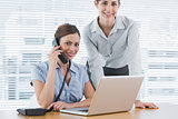 Businesswoman calling and smiling at camera with co worker