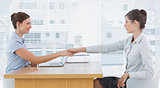 Businesswoman shaking hands with interviewee