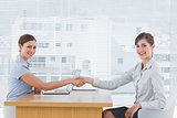 Businesswoman shaking hands with interviewee and both smiling at camera