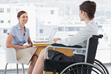 Businesswoman speaking with disabled colleague