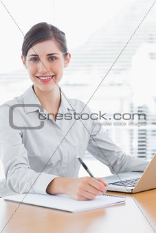 Pretty businesswoman working and smiling at camera