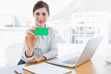Happy businesswoman showing green business card