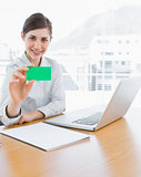 Pretty businesswoman showing green business card