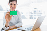 Young businesswoman showing green business card