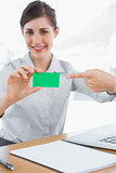 Happy businesswoman pointing to green business card