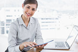 Businesswoman using digital tablet smiling at camera